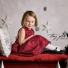 Young Girl in red dress sitting on red bench for Christmas Minis