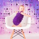 Violet Bubble Curtain Backdrop with toddler dressed in purple sitting on white chair
