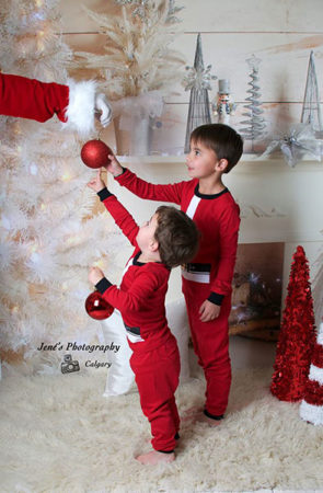 Santa arm with two young boys in Christmas pajamas