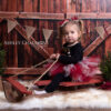 Little girl sitting on sleigh posing for Christmas mini session