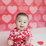 Valentine's Day Mini Session with Baby Girl and red hearts backdrop