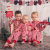 Three Brothers posing for Christmas mini session in red striped pajamas