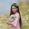Easter Photoshoot with Girl holding a Bunny with a field of daisies backdrop