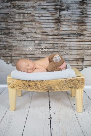 Newborn sleeping on bench beside broken wall backdrop