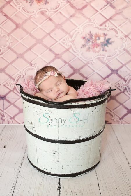 Newborn sleeping in wooden bucket beside pink floral backdrop