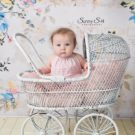 Baby girl sitting up in white carriage in front of victorian backdrop