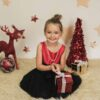 Young Girl posing for Christmas mini session with star backdrop
