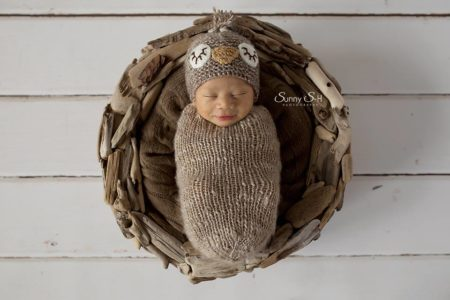Newborn wearing crocheted owl hat in bowl