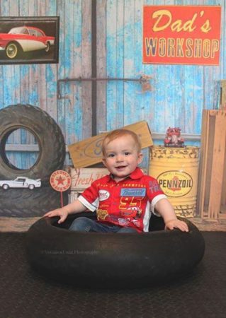 Dad's Workshop with little boy smiling in tire