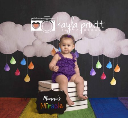 Young girl sitting on crate in front of Rainbow Chalkboard photography backdrop