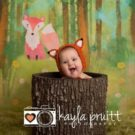 Newborn dressed in fox hat peeking out of hollow tree trunk