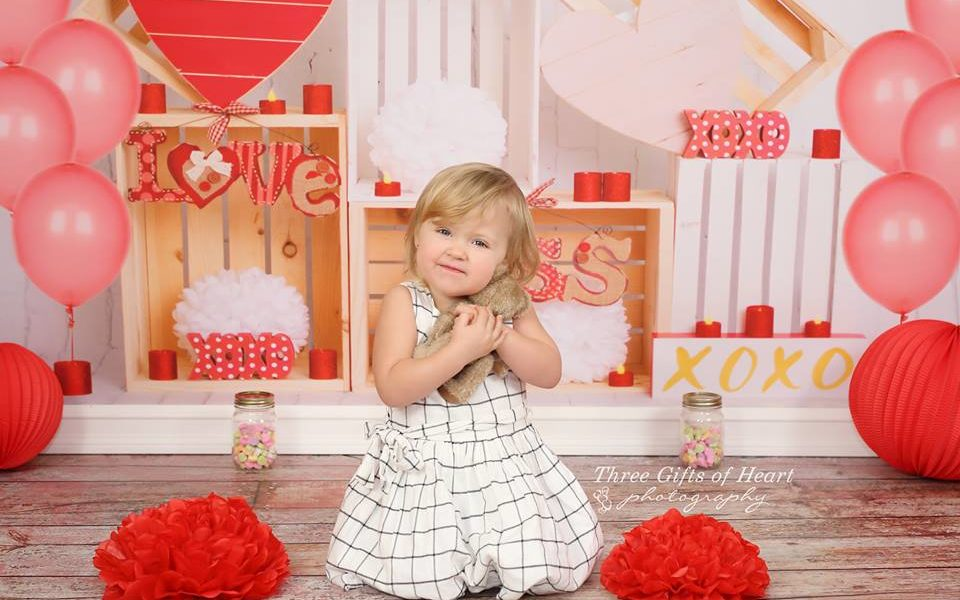 Valentine's Day Photography Backdrop with young girl holding a stuffy