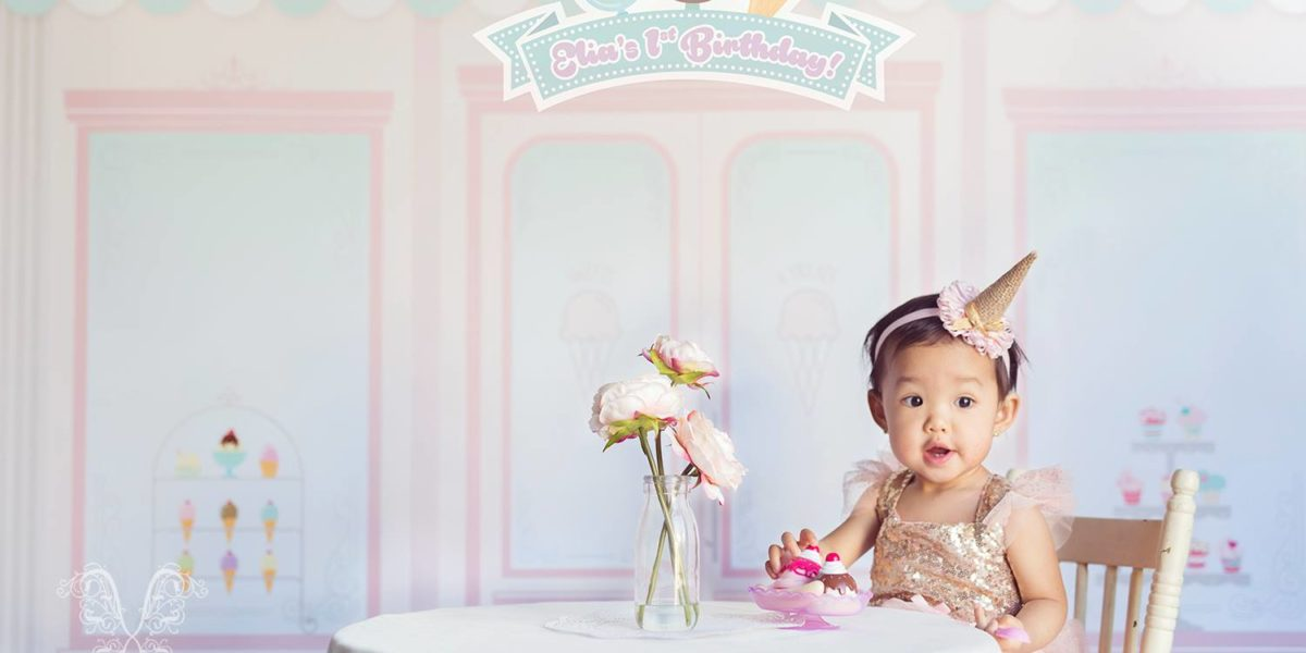 Custom Birthday Backdrop featuring storefront with baby sitting at a table