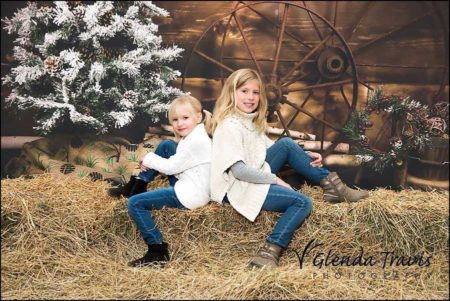 Rustic Christmas themed photoshoot with girls on bales of hay