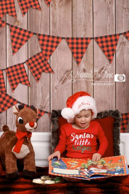 Young Girl Reading a Christmas Book with Lumberjack banner backdrop