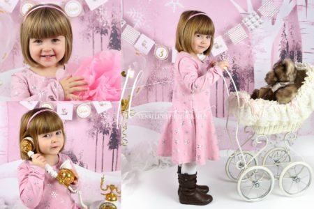 Young Girl Pushing Vintage Baby Carriage with Pink Snowdrift Forest Backdrop