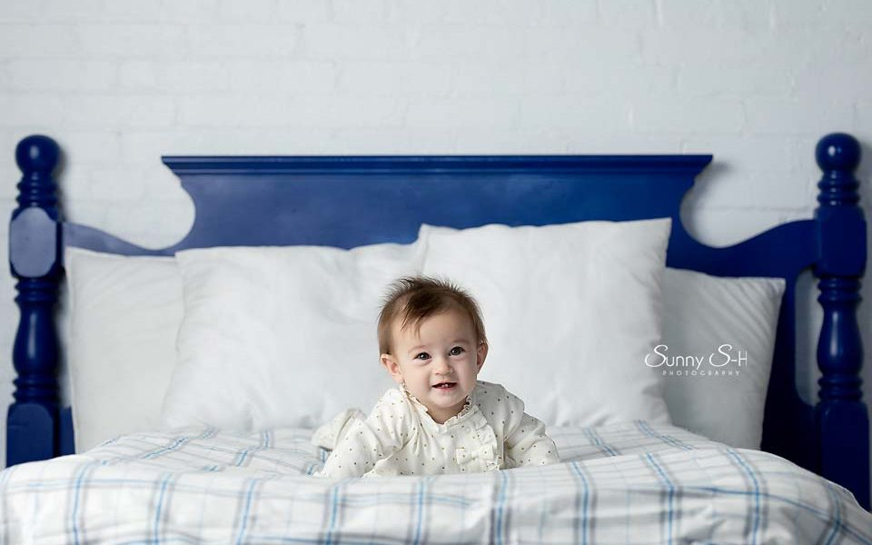 Baby posing on bed with Solid Blue Headboard backdrop