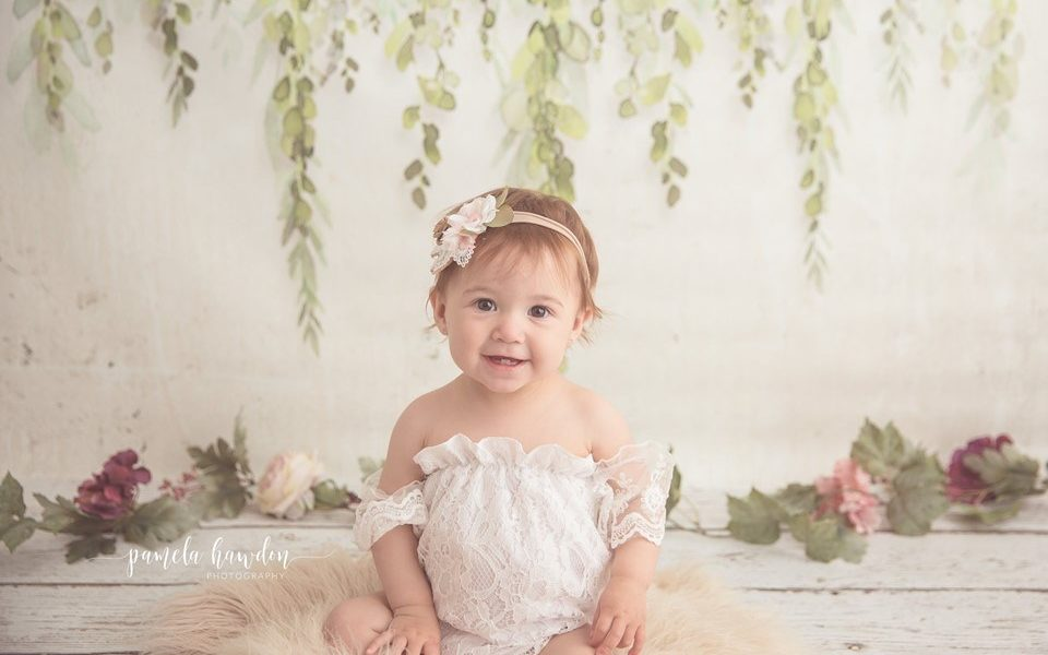 Toddler sitting posing for photoshoot using floral swag backdrop