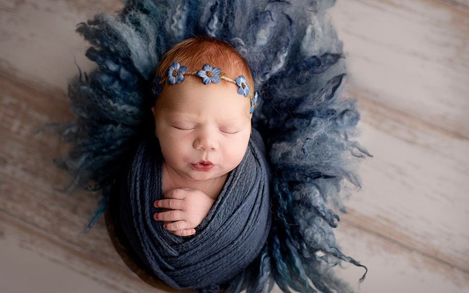 Newborn posed for photoshoot using white distressed wood floordrop