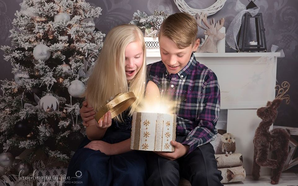 Brother & Sister opening present in front of Christmas backdrop