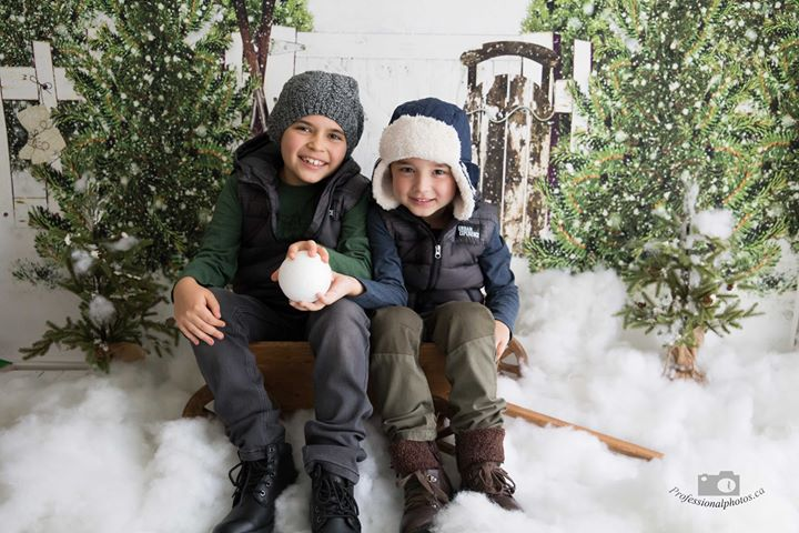 Two boys sitting on sled for Christmas photo session