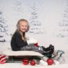 Christmas Session of Girl on Sled in front of Winter Backdrop Scene